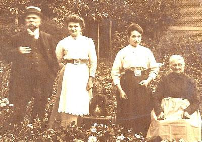 De familie Neomagus-Vosters in Ekeren met de dochters Tilly en Marie. De foto is genomen vóór 23 september 1910, de sterfdag van vader Frits. Tilly en Marie gaan in januari 1911 met moeder Julia naar Borgerhout, waar ze de kruidenierswinkel voortzetten.