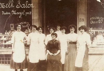 Het beroep van Emma in Brussel is 'melksalonhoudster'. Victor Moeys is eigenaar van de zaak, zoals de tekst op de etalage aangeeft. Volgens de overlevering heeft Emma een verhouding met hem. De foto toont Emma omringd door het personeel van de salon, omstreeks 1910.