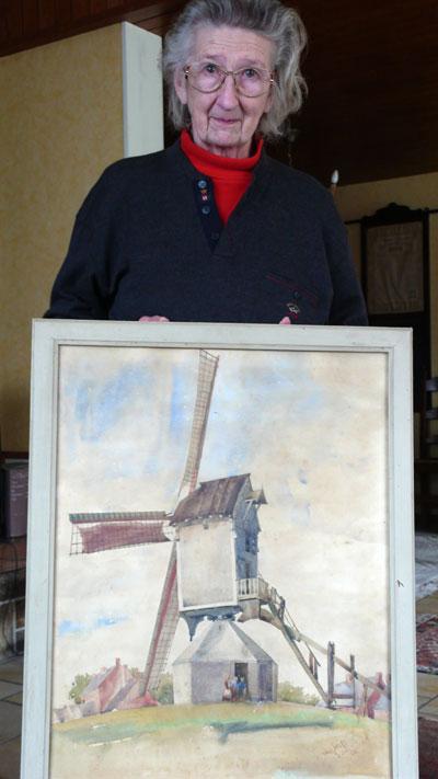 Daisy Ommeganck-Pillot, weduwe van Robert Ommeganck die een kleinzoon is van Clemence Denissen-Neomagus, poseert in 2009 bij een schilderij van de molen van Denissen in Essen.
