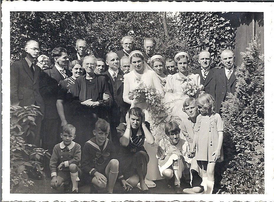 Familiefoto, op de trouwdag 15 september 1938 gemaakt in de tuin van Berry's ouderlijk huis, Goirkestraat 169 in Tilburg. De ouders van de bruid zijn Janus van Riel (zijn hoofd is net zichtbaar tussen het bruidspaar) en Koosje Broeders (links van de bruidegom die haar een arm geeft). De ouders van de bruid zijn Poliet Neomagus (helemaal rechts) en Anna Weijermans (rechtsboven de bruid). De bruidsmeisjes zijn Julia (zus van Victor, achter de bruid) en José Ooms (nicht van Berry). Op de foto staan verder onder meer broers van het bruidspaar met hun vrouwen, neven en nichten.