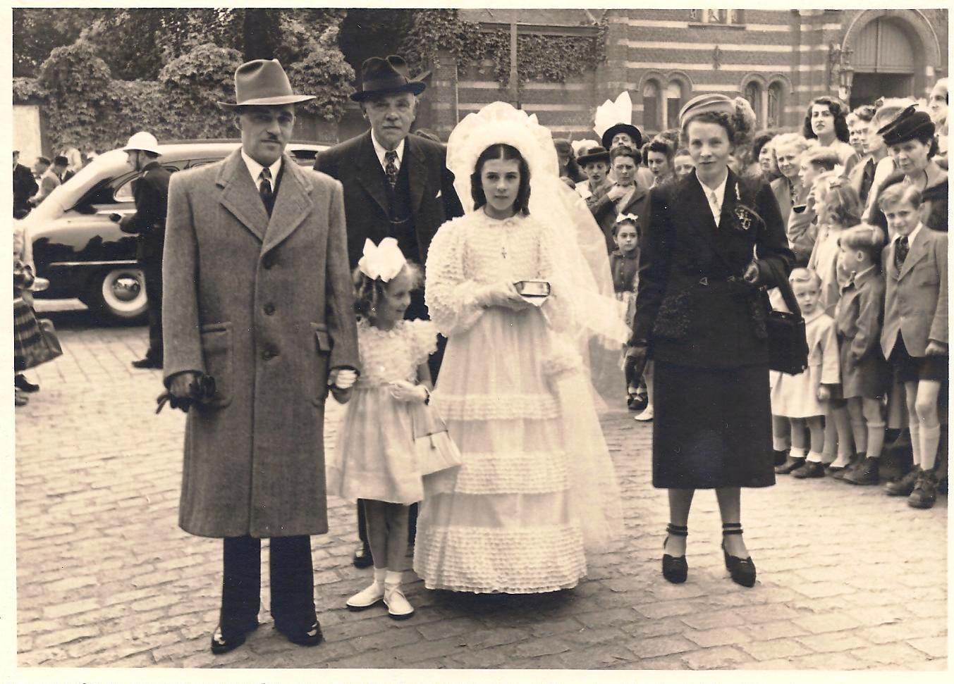 Dochter Lily ontvangt in 1949 het vormsel. Naast haar zusje Anny. Moeder Martha maakt beide jurken zelf. Op de achtergrond opa Victor.