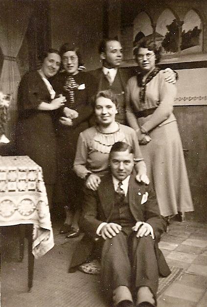 Frits (voorgrond) op bezoek in Oosterhout. Achter hem nicht Julia. Staand van links naar rechts zijn zus Marie, Annie Vlamings, pas getrouwd met Frits' neef André, Victor Neomagus en zijn aanstaande Berry van Riel. De foto is genomen in het najaar van 1935. Op de achtergrond is een deel te zien van een van de schilderingen die Witte Pater Frits in de veranda van het huis in Oosterhout heeft gemaakt.